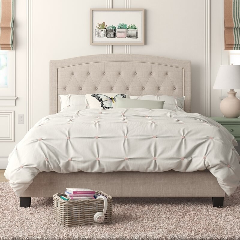 a made bed with a tufted beige comforter and a matching tufted headboard