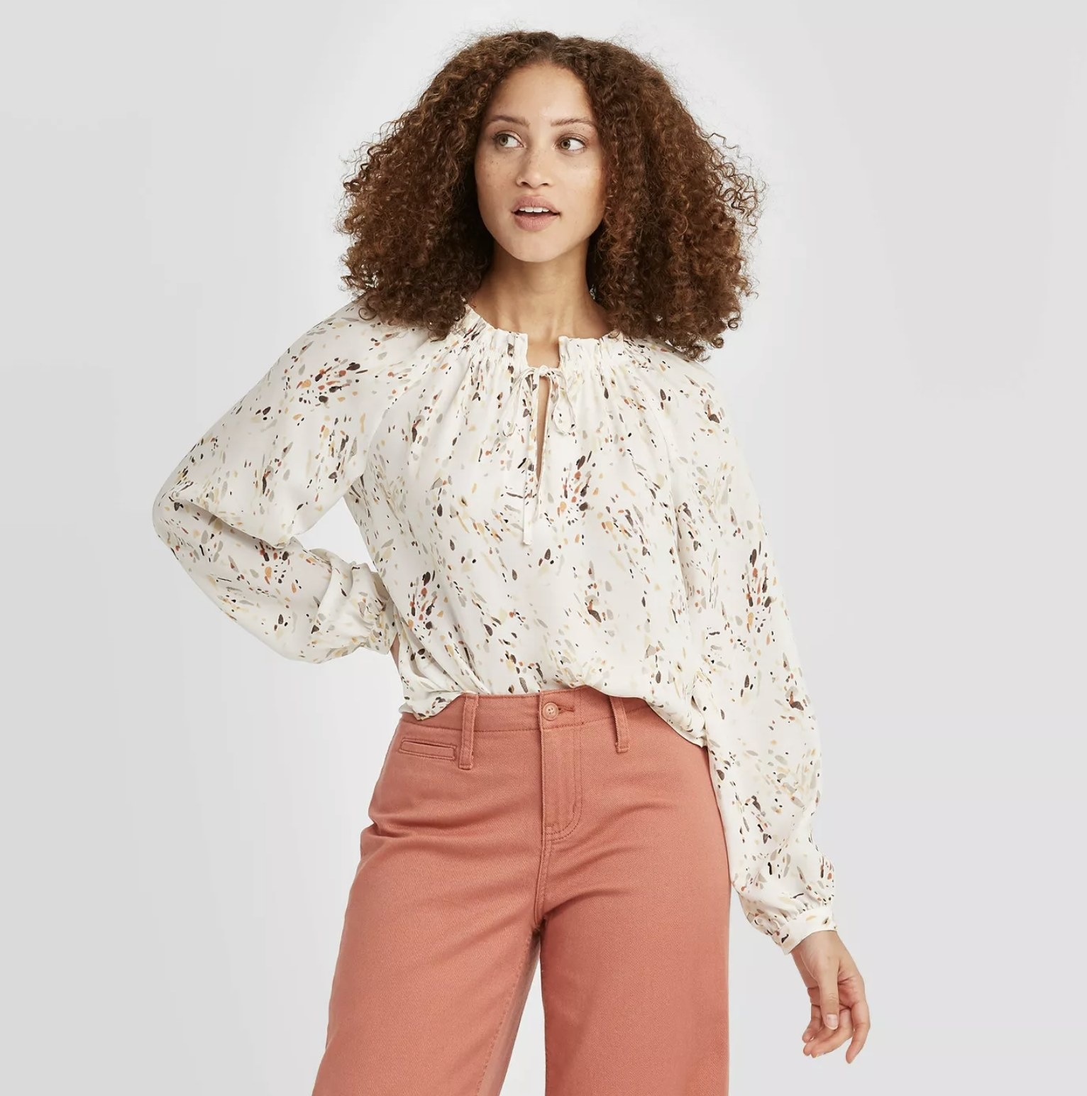 model wearing the sleeved white and floral blouse