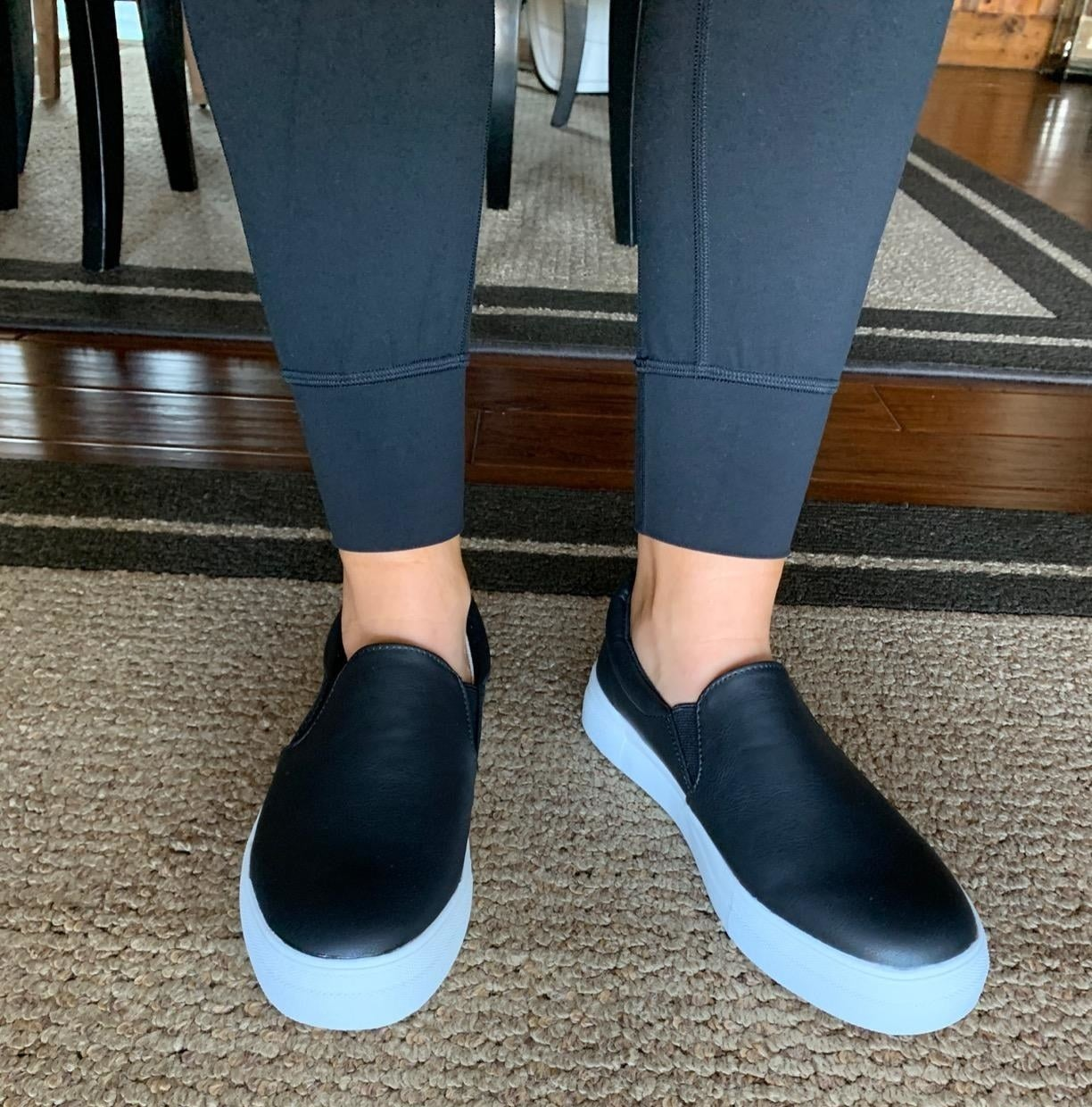 Reviewer wearing the slip-on sneaker in black with a white wide sole