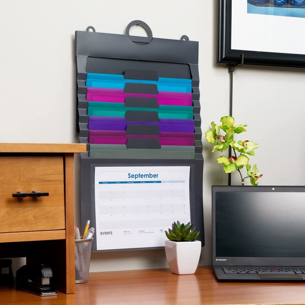 The wall organizer on the wall of an office with a calendar in the transparent bottom pocket