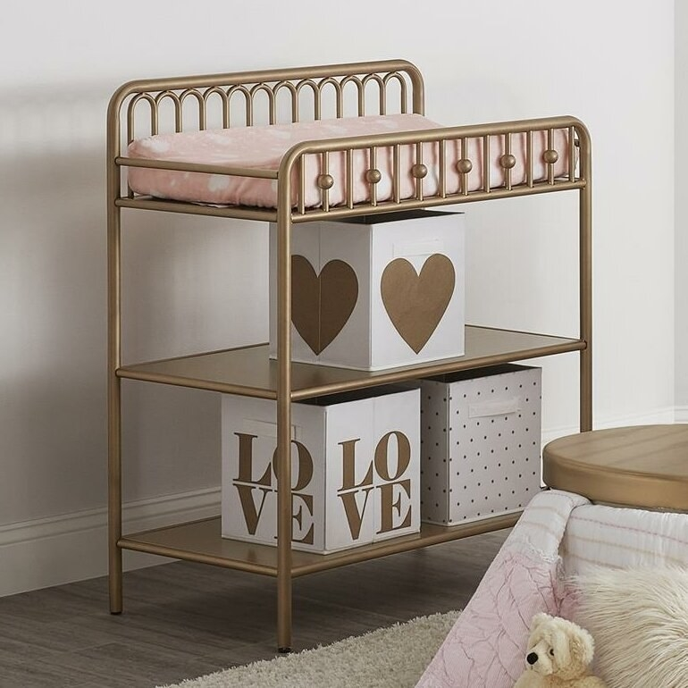 A three-tier changing table with the bottom tiers for open storage. It's gold and has rails on each side of the table at the top plus a pink cushion.