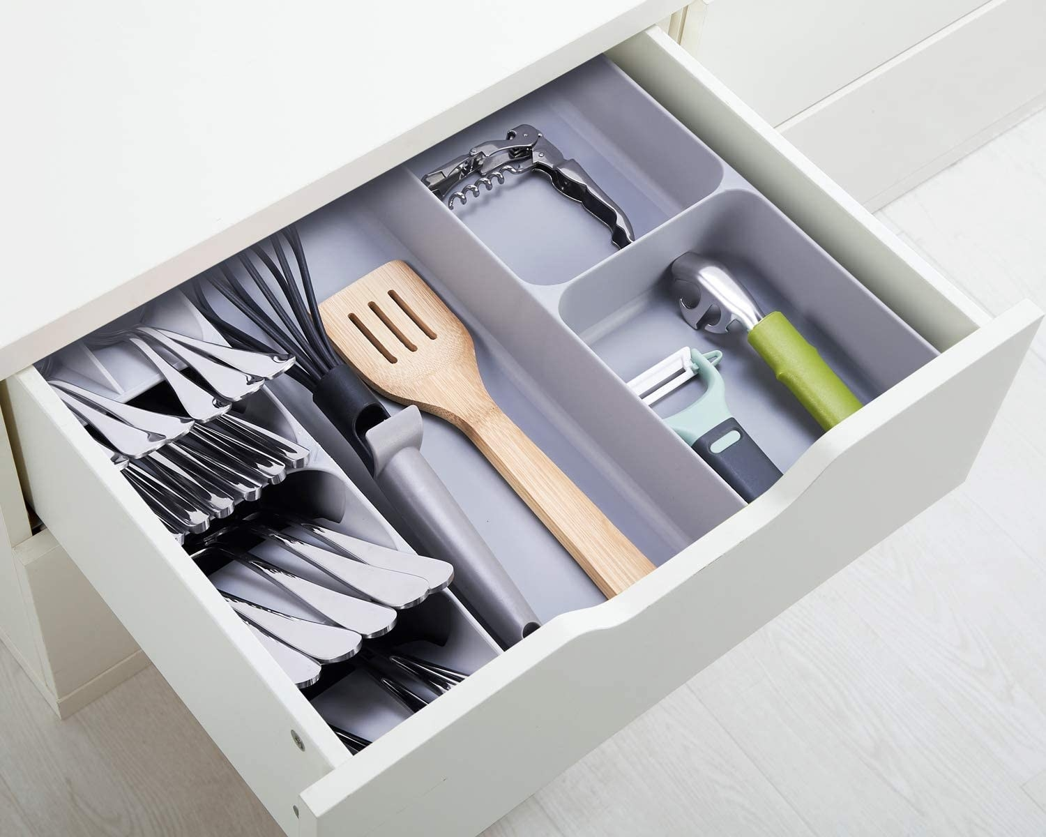 The cutlery tray in a drawer filled with utensils and cooking tools