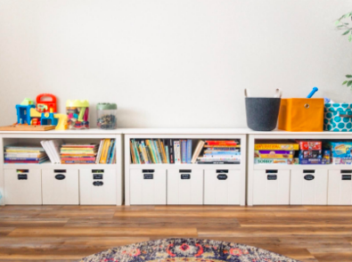 A reviewer's image of three sets of cubby shelves being used to store books and toys in an orderly fashion.
