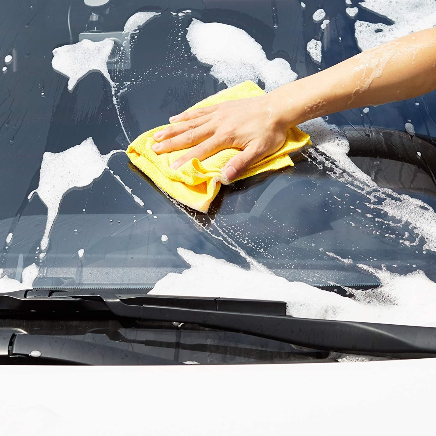 Model using a yellow microfiber towel to wash a windshield