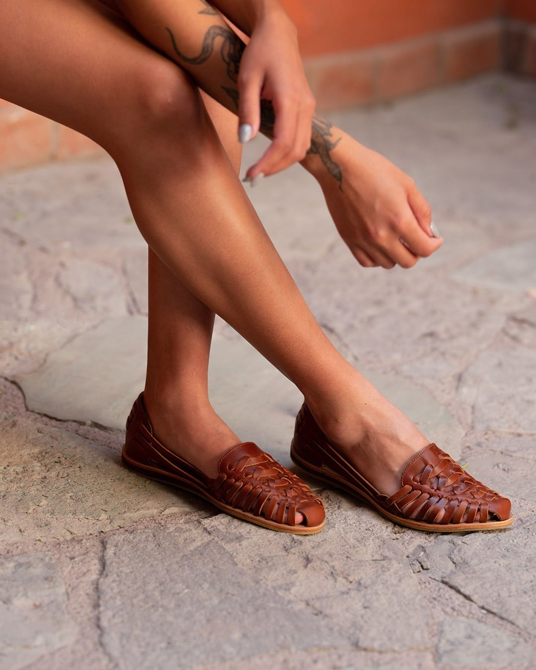 Model wearing the handwoven flats in brown