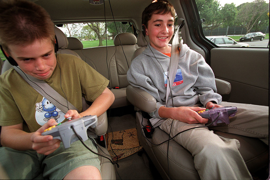 Two boys playing Nintendo 64 in the back of a car.