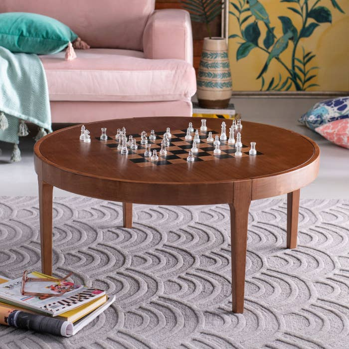 A round brown coffee table with a chessboard pattern on the tabletop