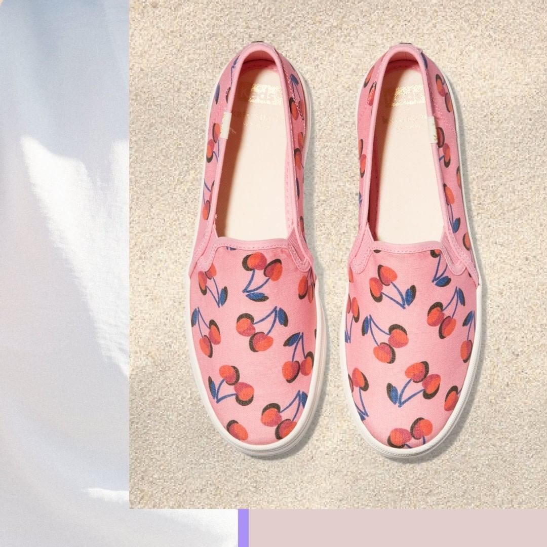Top view of slip-on shoes in pink with illustrations of red cherries with blue stems all over them