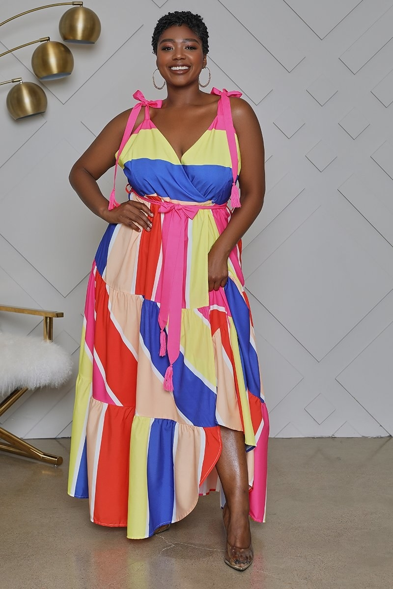 A model wearing the V-neck, tie-waist, ruffle-hemmed dress with thick peach, red, yellow, blue, and white stripes