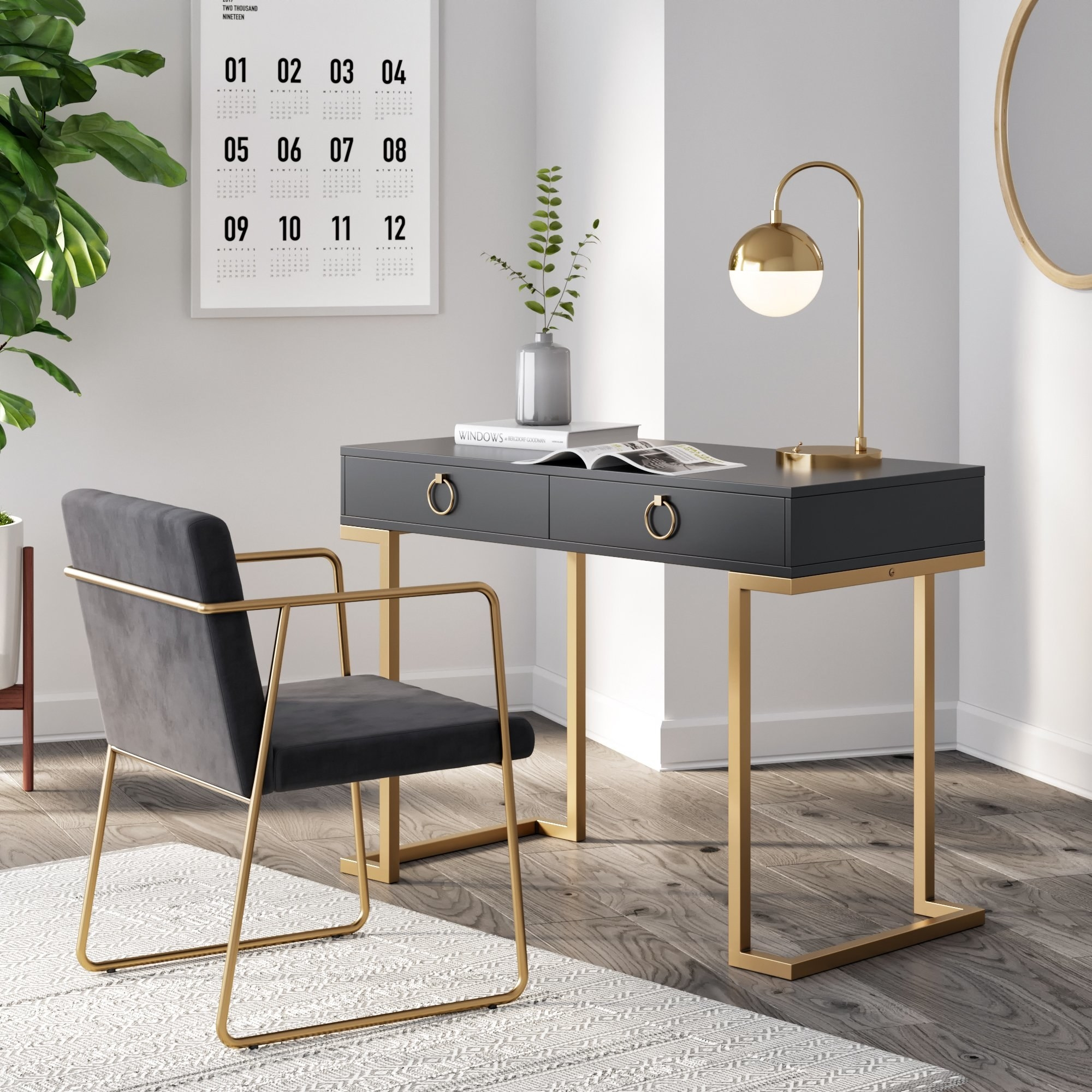 A black desk with round gold drawers knobs and open gold legs