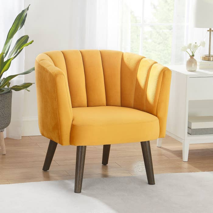A mustard yellow chair with full back and arms and brown wooden legs