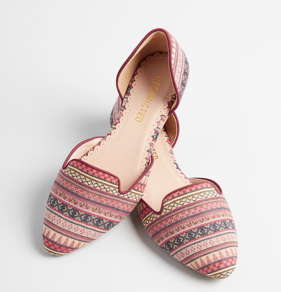 The pointed-toe flat with tonal stripes and a geometric pattern in pink, red, black, and yellow