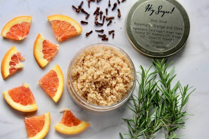 A flat lay shot of the brown scrub in a labeled jar with the lid off and raw ingredients of citrus, rosemary, and clove around it