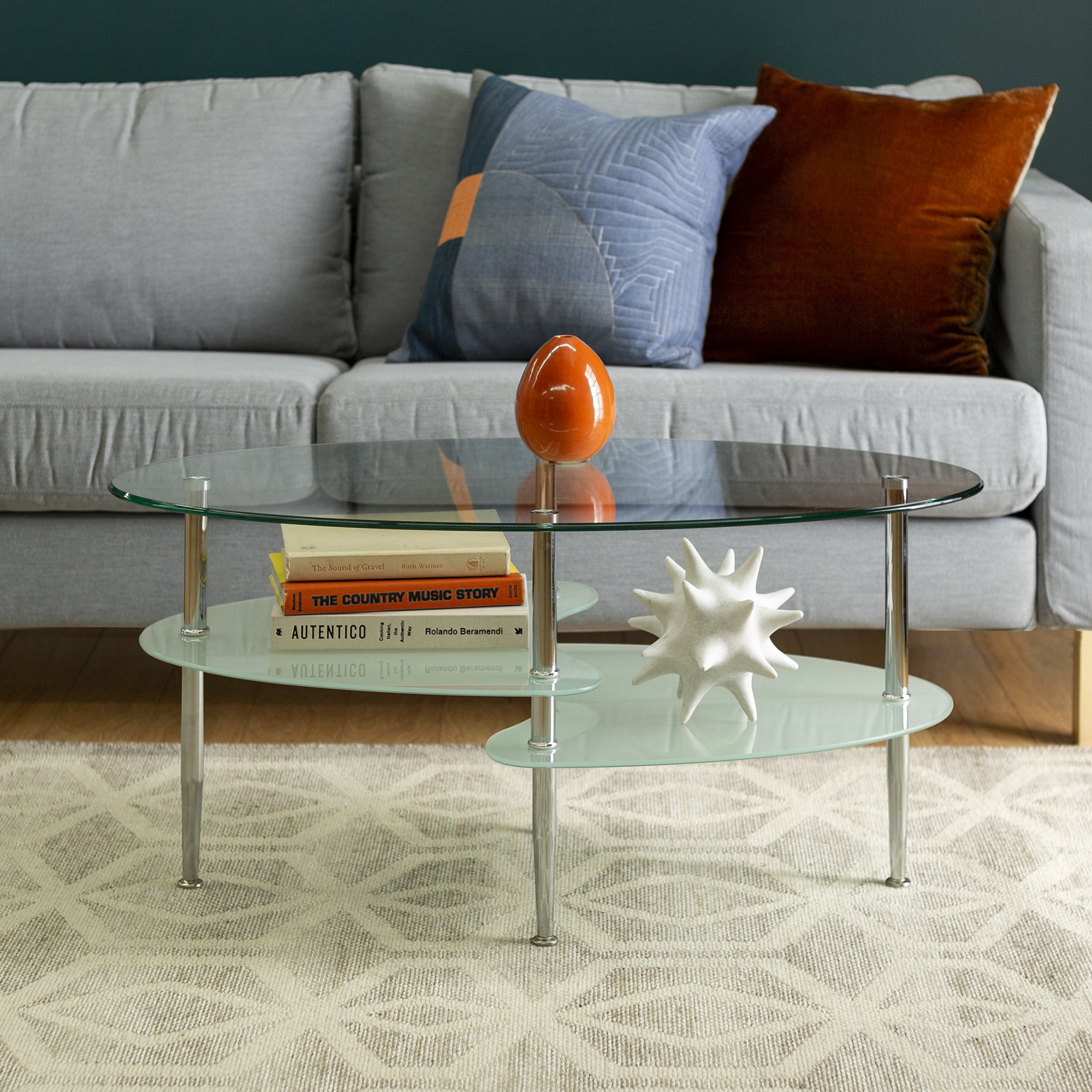 A glass coffee table with silver metal legs and two shelf spaces