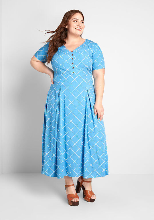A reviewer wearing the short-sleeve dress printed with white lines and with a button detail on the bodice