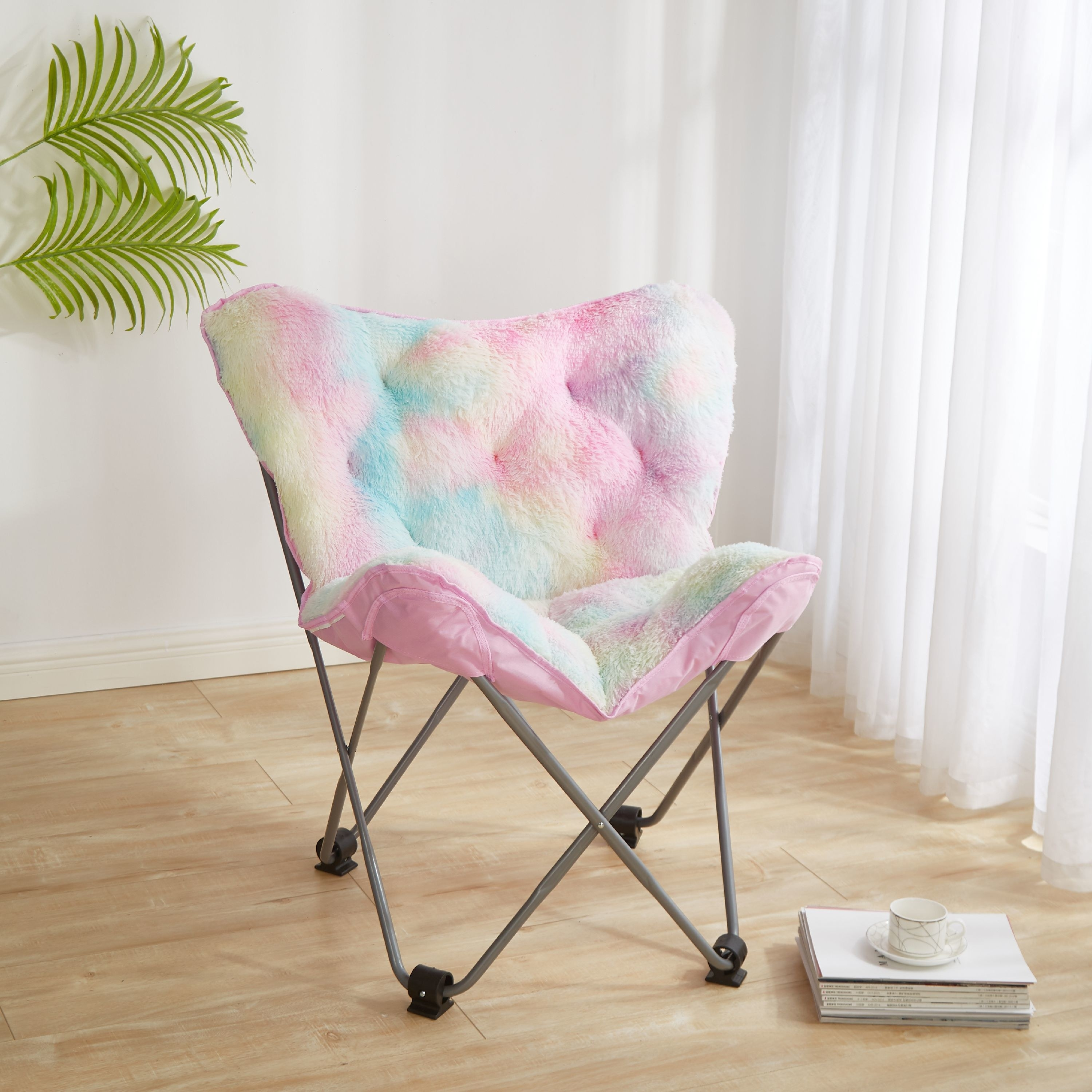 A folding chair with thin metal legs and rubber stopper with a light-colored rainbow cushion