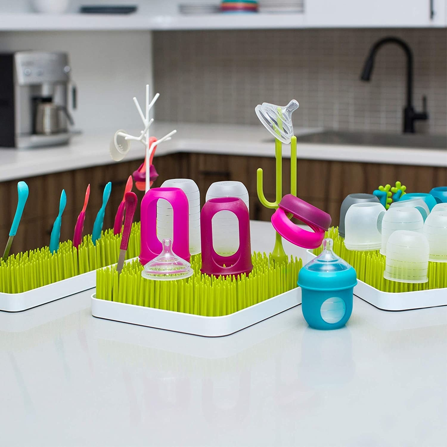 The drying racks on a kitchen counter with baby bottles perched on top of the grassy nodes