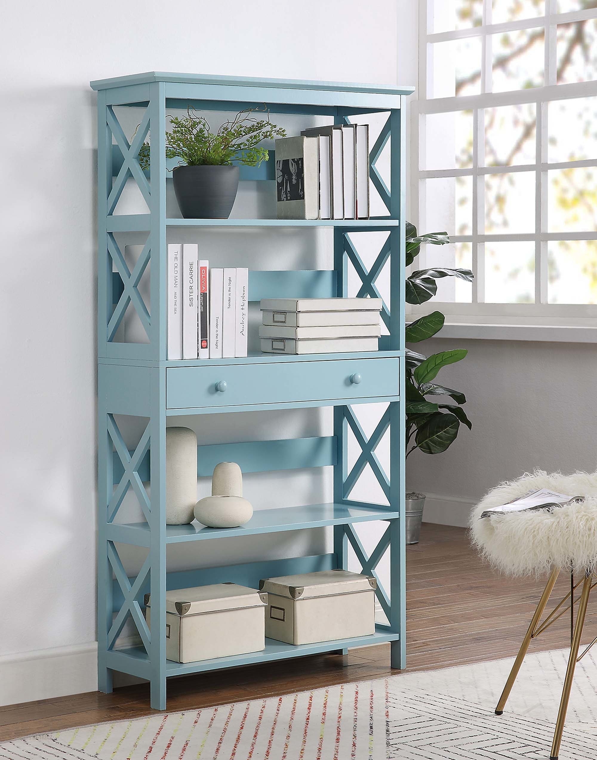A sea-foam colored bookshelf with a drawer in the middle separating two shelves on the bottom and two on the top