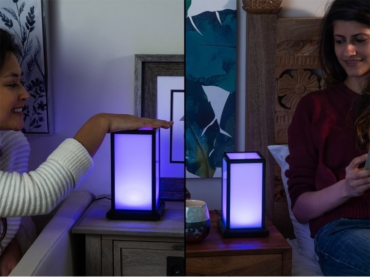A split image of two models with the rectangle lamps on their bedside table with one model touching the top and the other model looking at theirs while both lamps are lit up purple