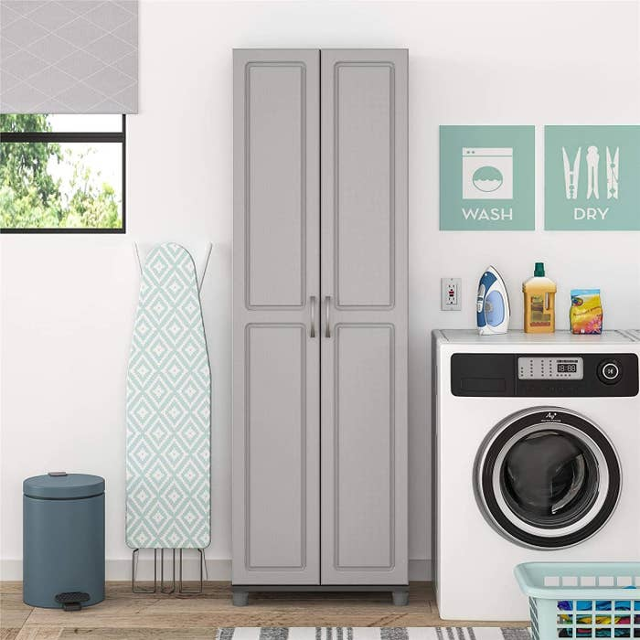 A tall and thin cabinet with two doors in grey in a laundry room