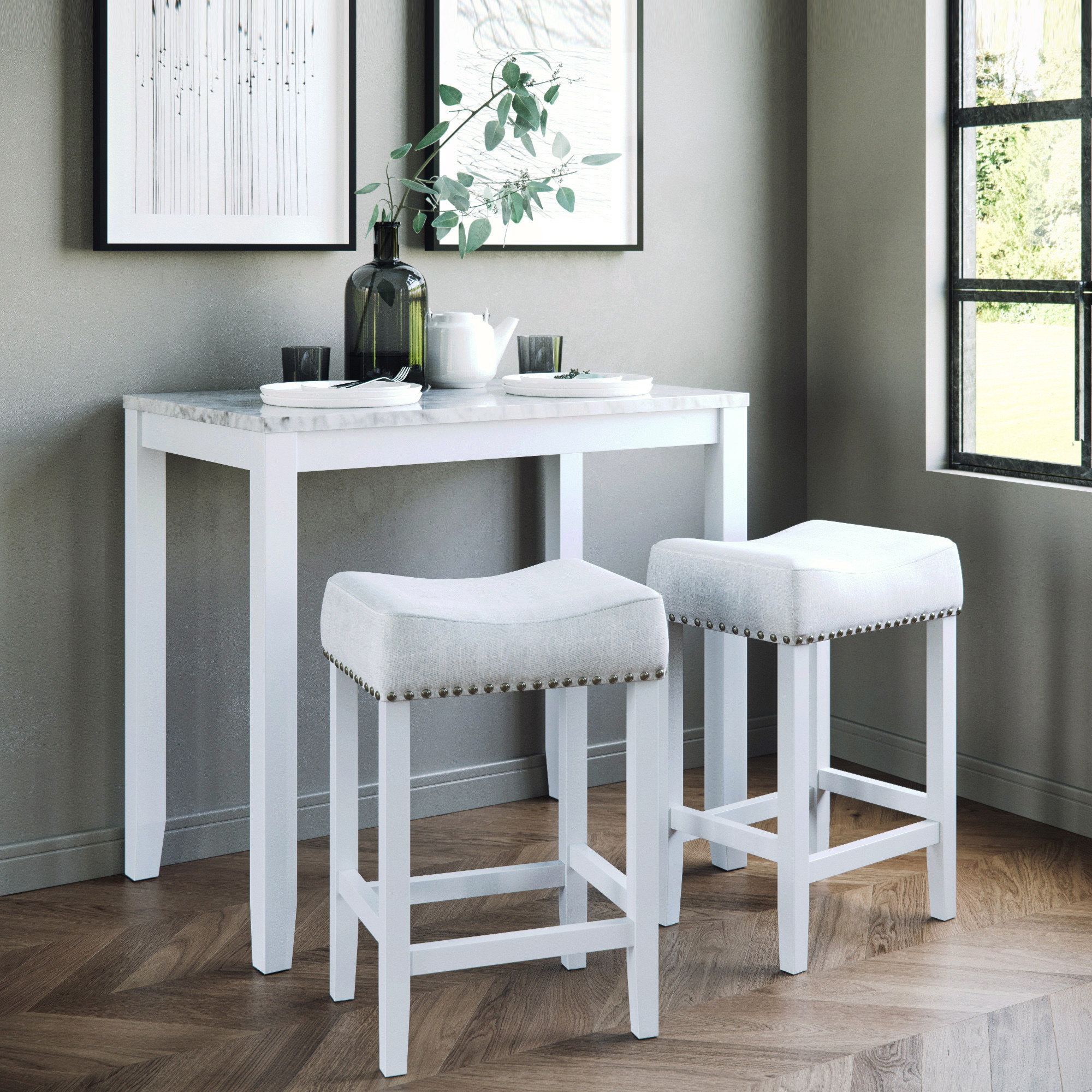 A table with a marble top and white wood base and two seats with light gray fabric tops