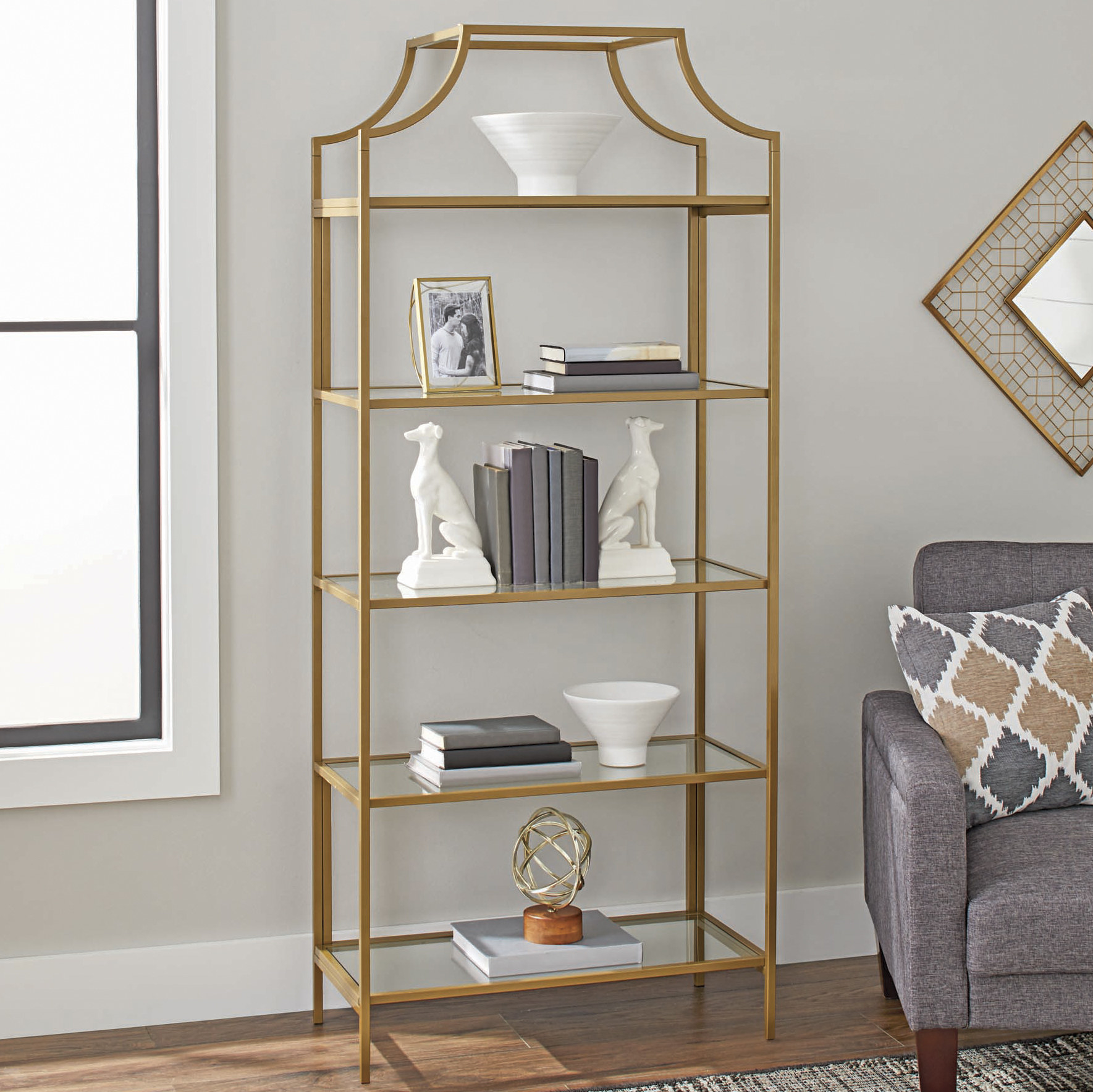 A gold-framed bookcase with five glass shelves