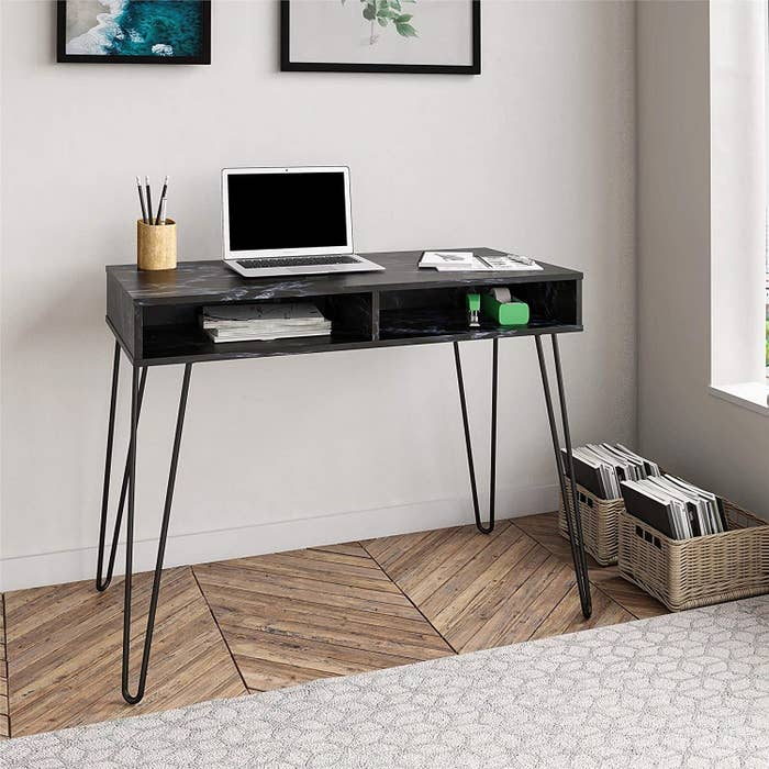 A simple black desk with two open storage shelves and wire legs