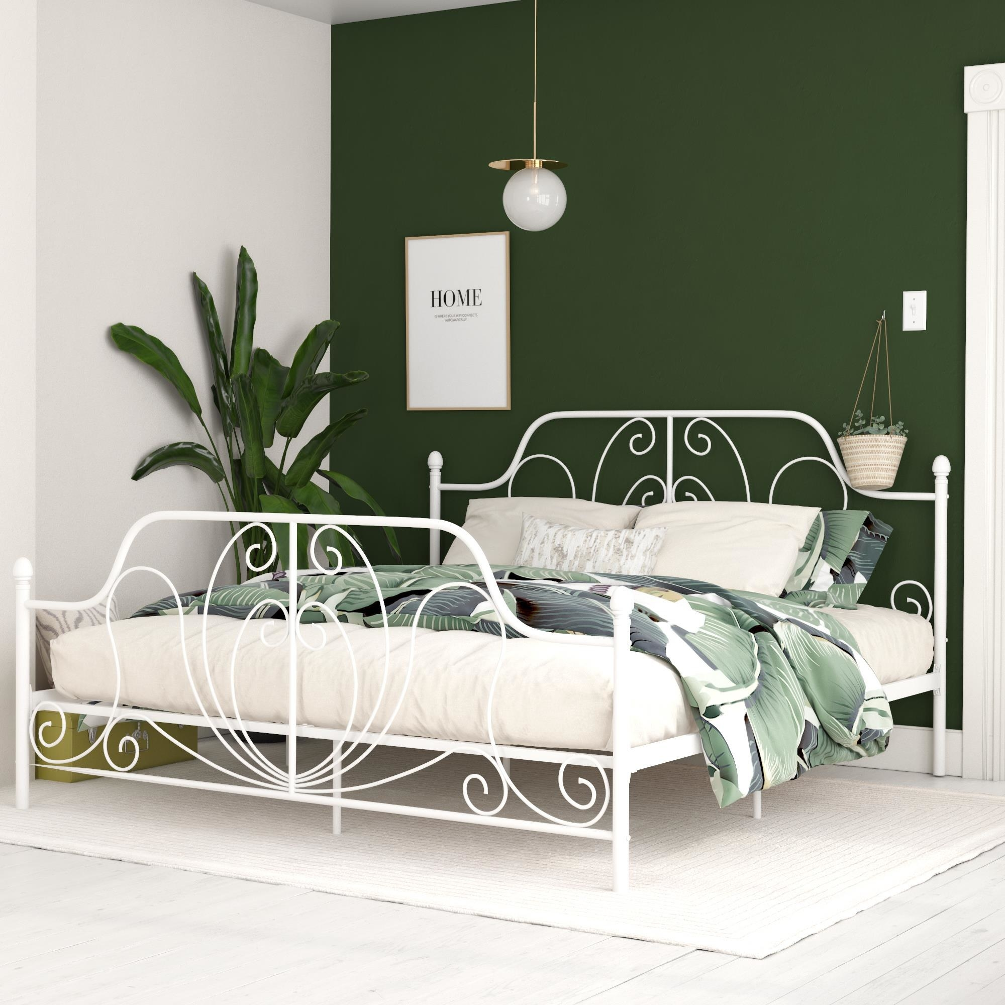 A white metal bed frame with four posts and an ornate design at the foot of the bed and the headboard