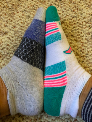 A reviewer wearing two mismatched pairs of socks from the pack. The socks rest at the ankles with a slightly higher, lightly cushioned end above the heel.