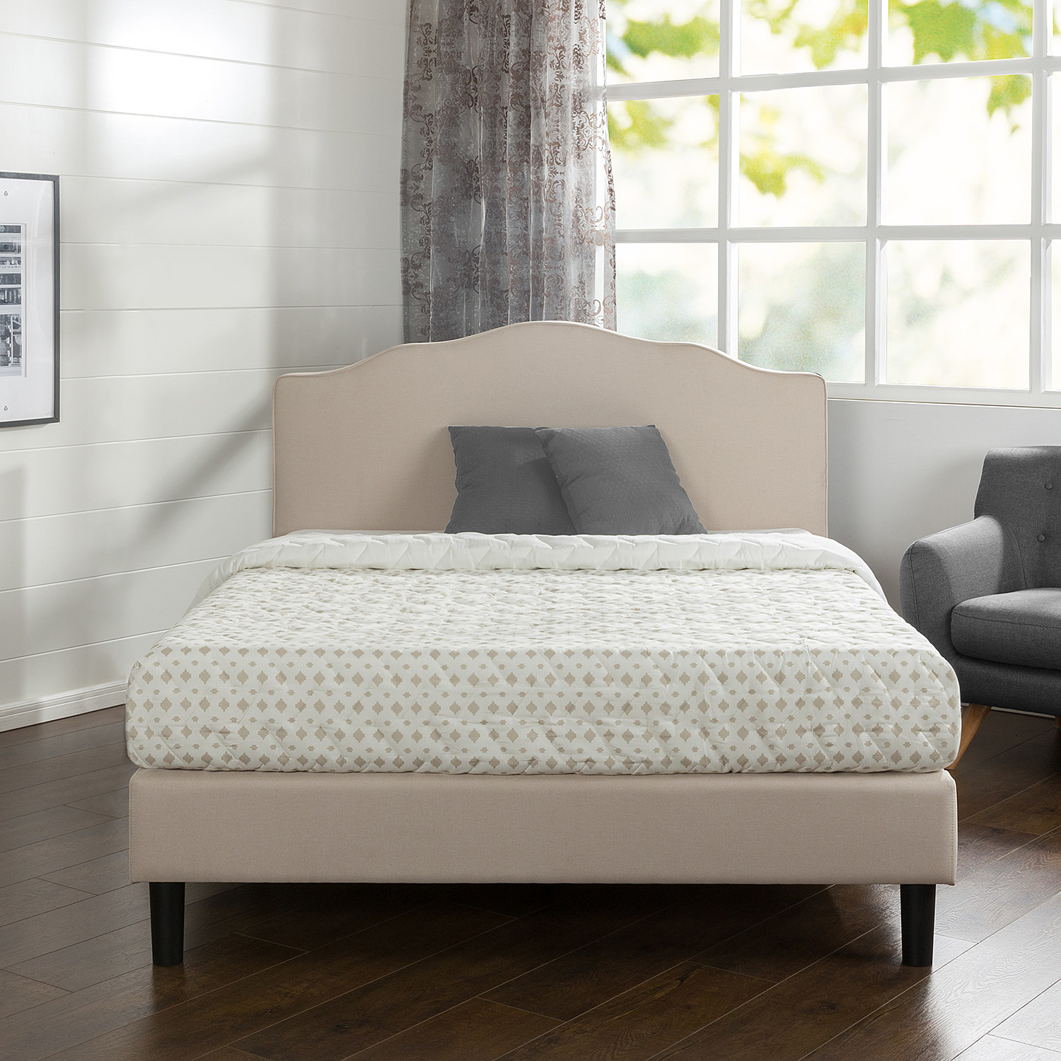 A cream-colored bed frame with headboard and brown wooden legs