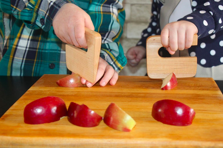Two kids cut apple slices on a cutting board