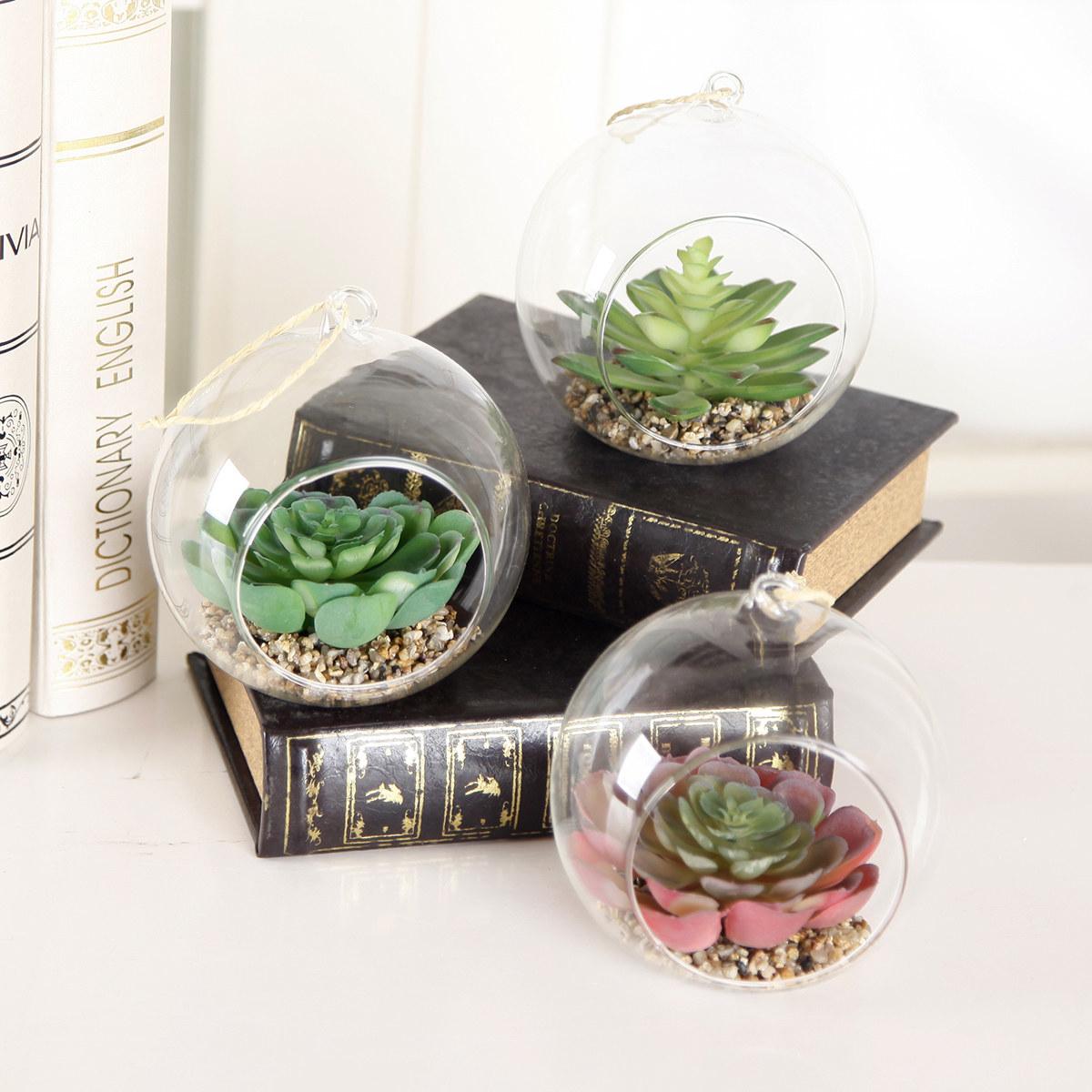 Three fake succulents in open round glass terrariums