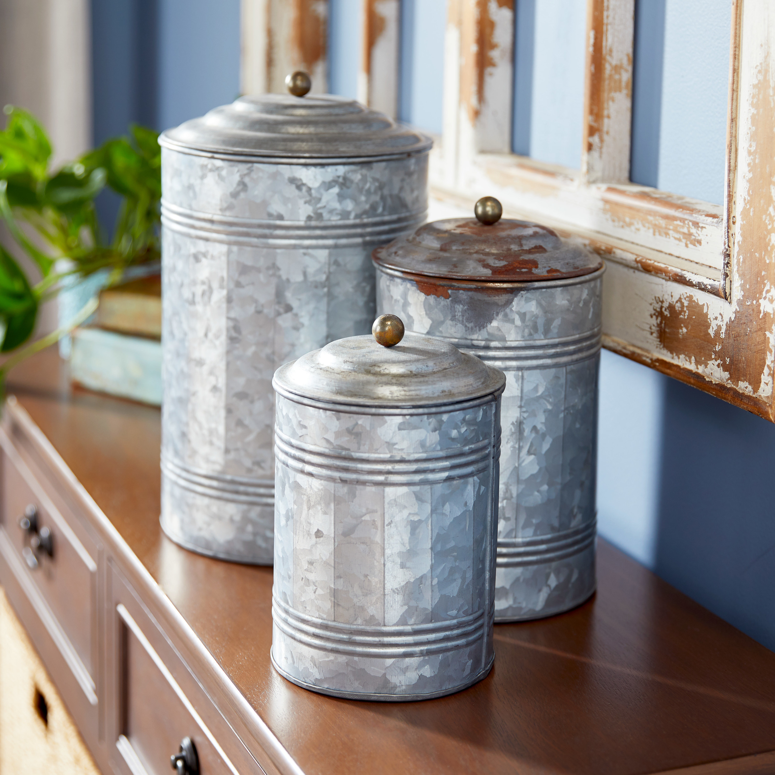 Three different sized, weathered-looking galvanized metal jars
