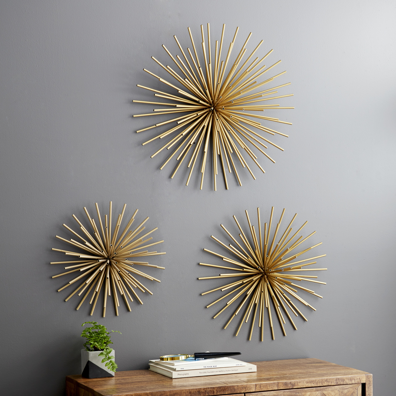 Three walk sculptures that look like golden straws forming a starburst