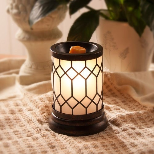 A bronze wax warmer with a black top and bottom with a glass bronze accents