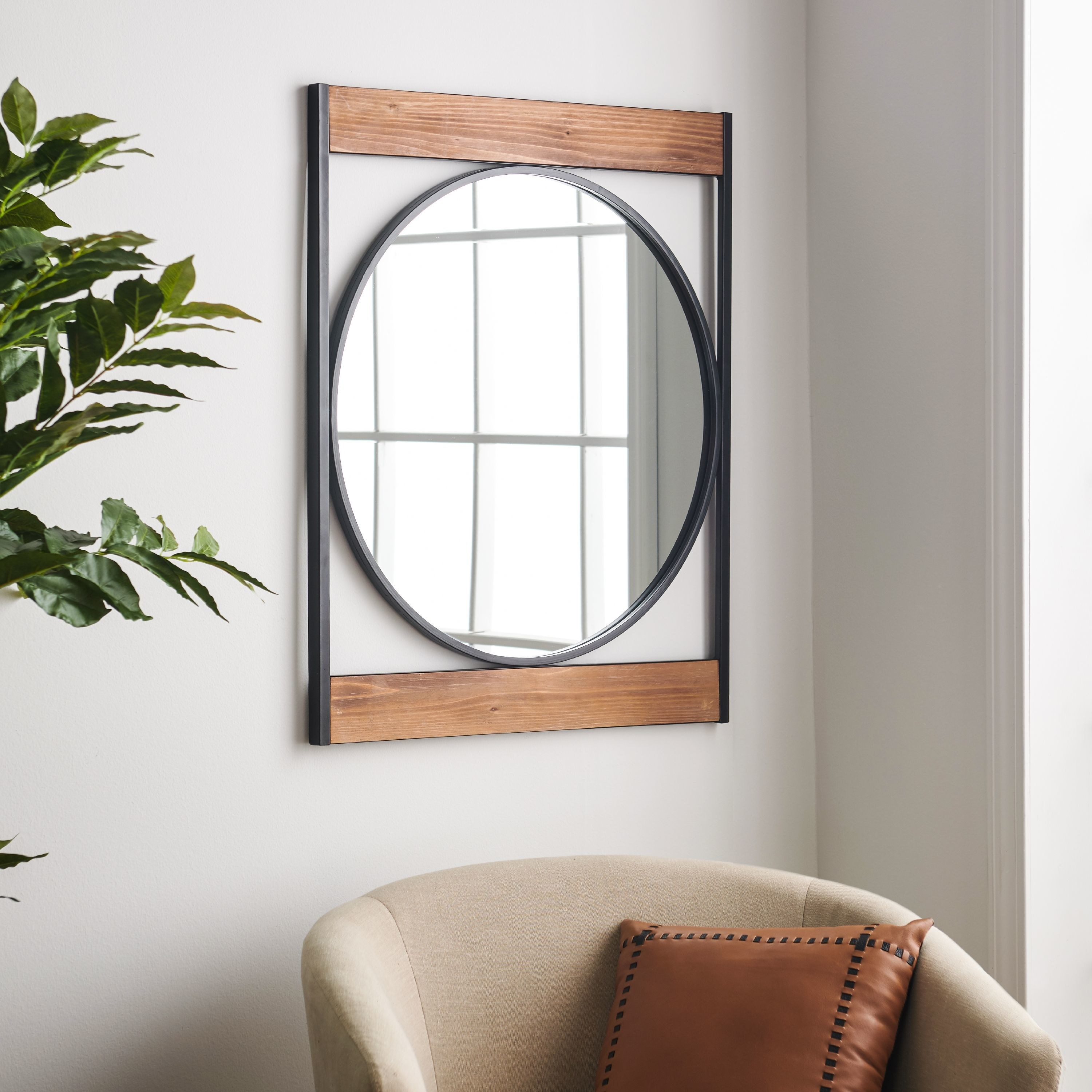 A circular mirror with a black metal frame situated between two horizontal pieces of wood and two vertical metal frames