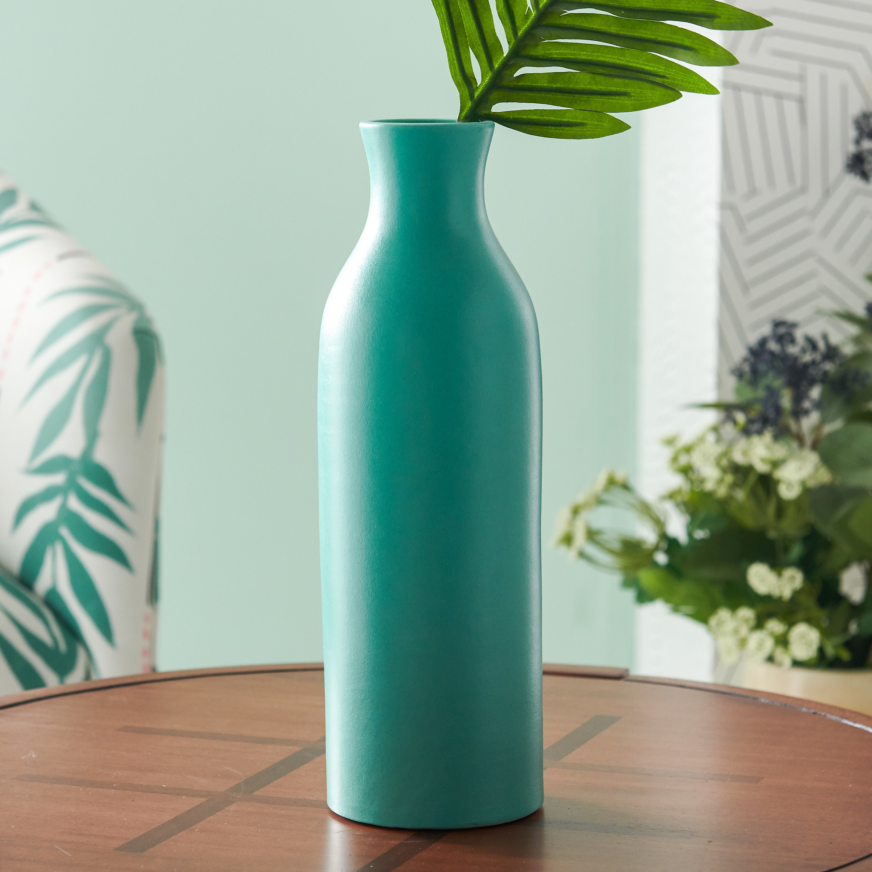 An aqua-colored round, narrow, and tall vase