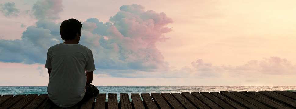 A man sits on a pier staring out at the ocean at sundown