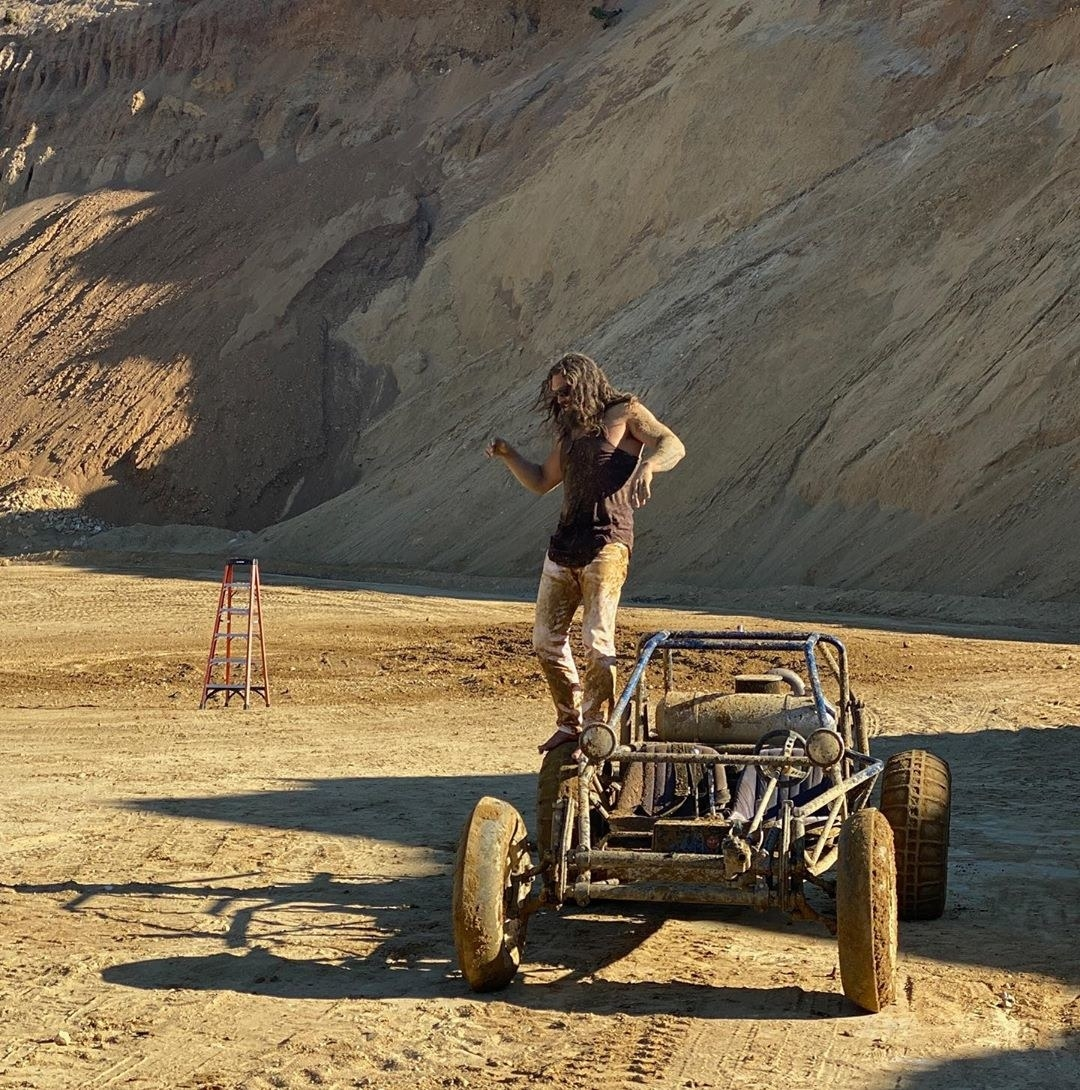 Jason Momoa standing on the side of a dune buggy