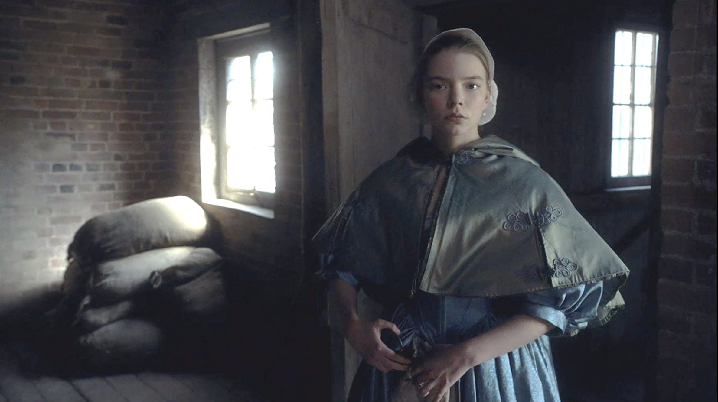 Anya Taylor-Joy in period garb, standing by a window