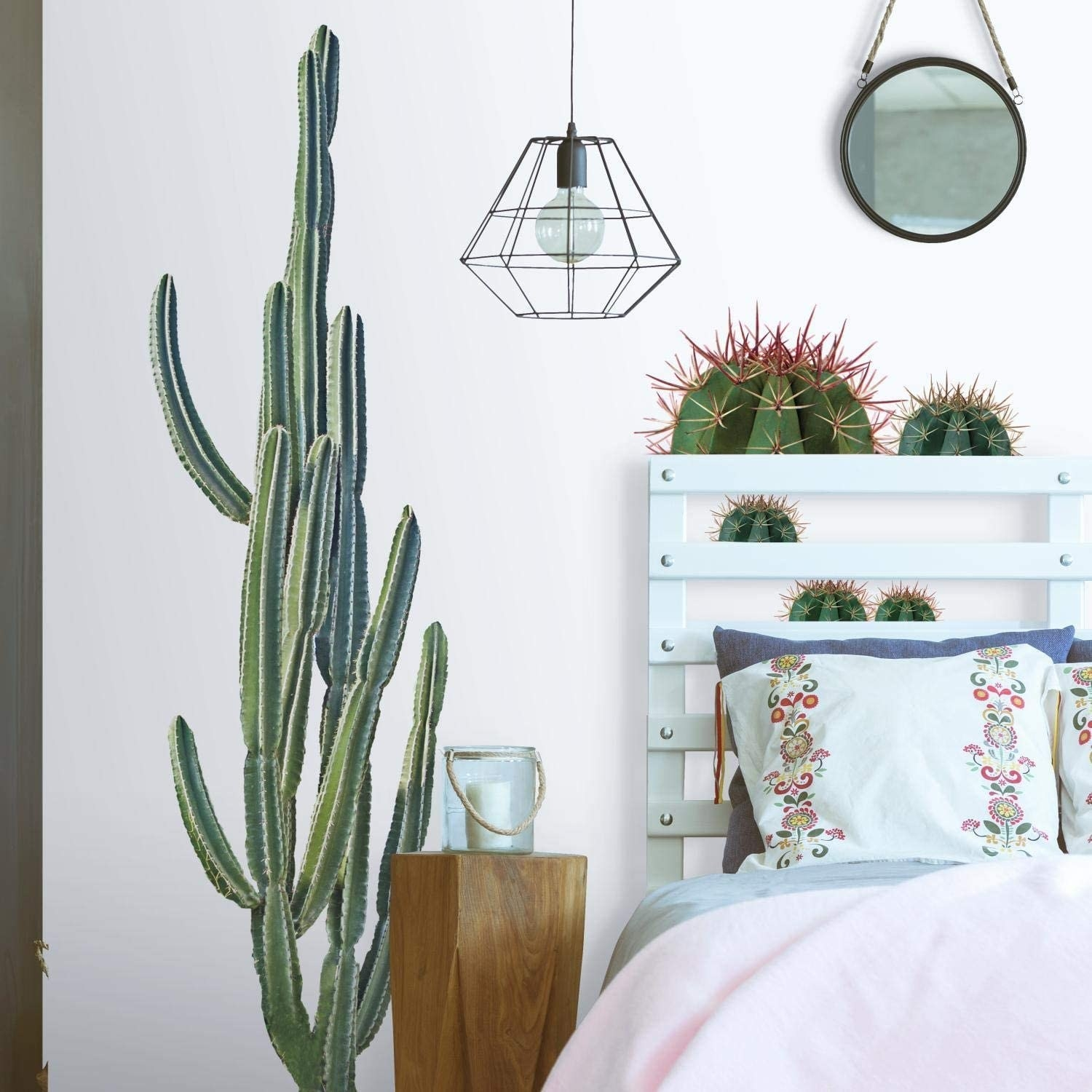 Four cactus wall decals on a bedroom wall behind a bed and nightstand