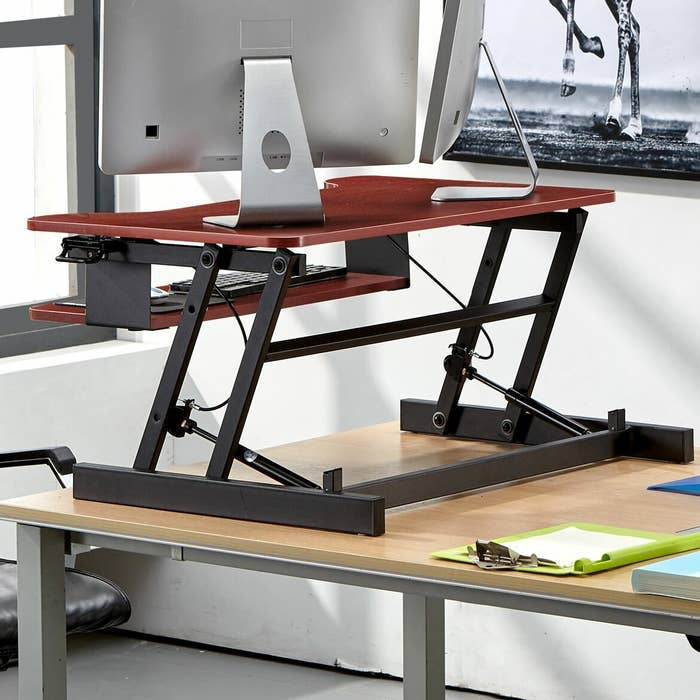 A red standing desk propped on a table with two monitors on top of it