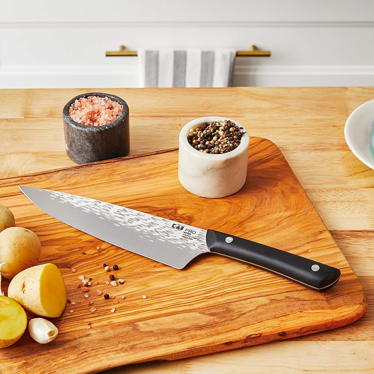 a fancy chef's knife with a black handle on a cutting board