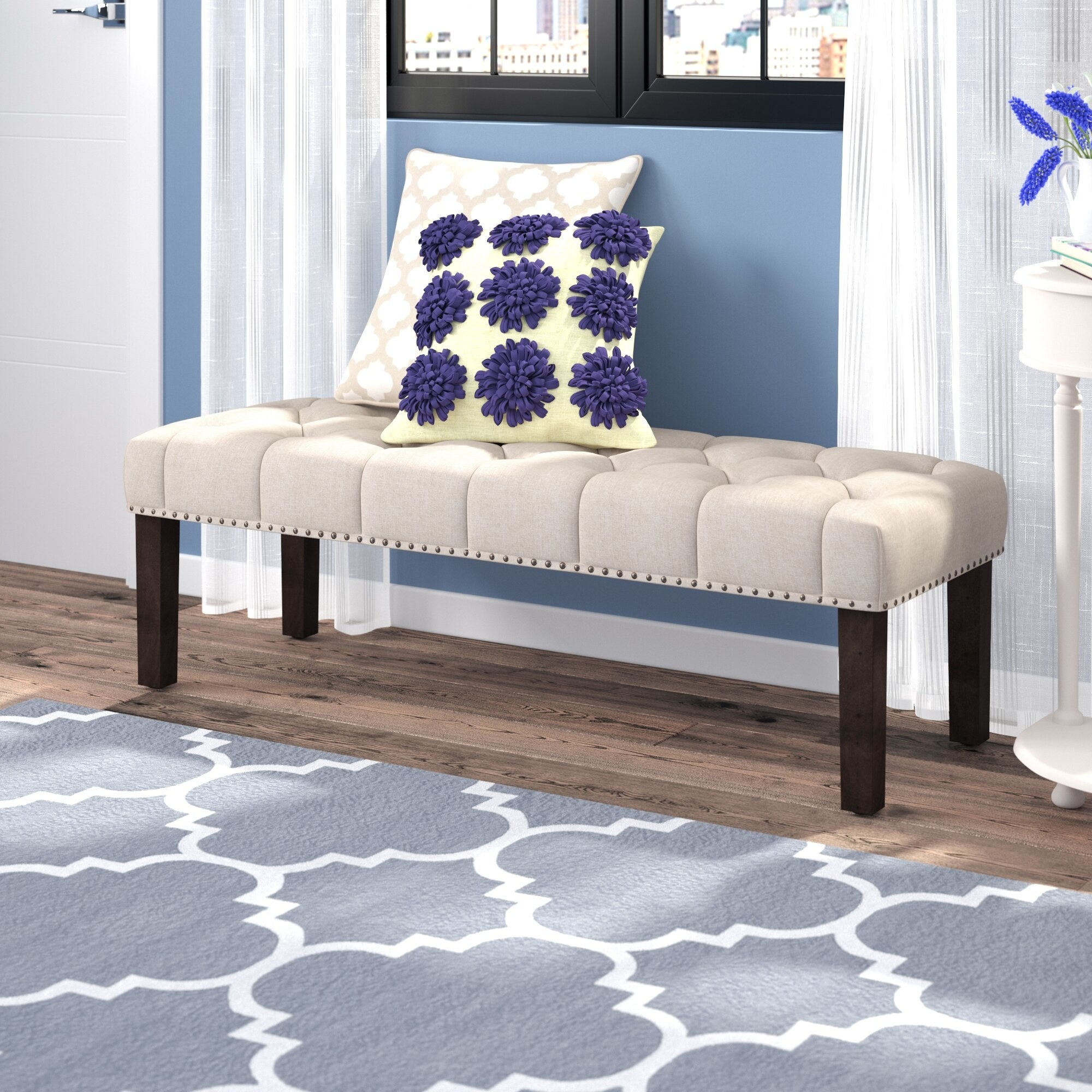 A white upholstered bench in a living room