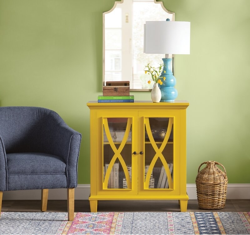 A yellow cabinet with glass window doors