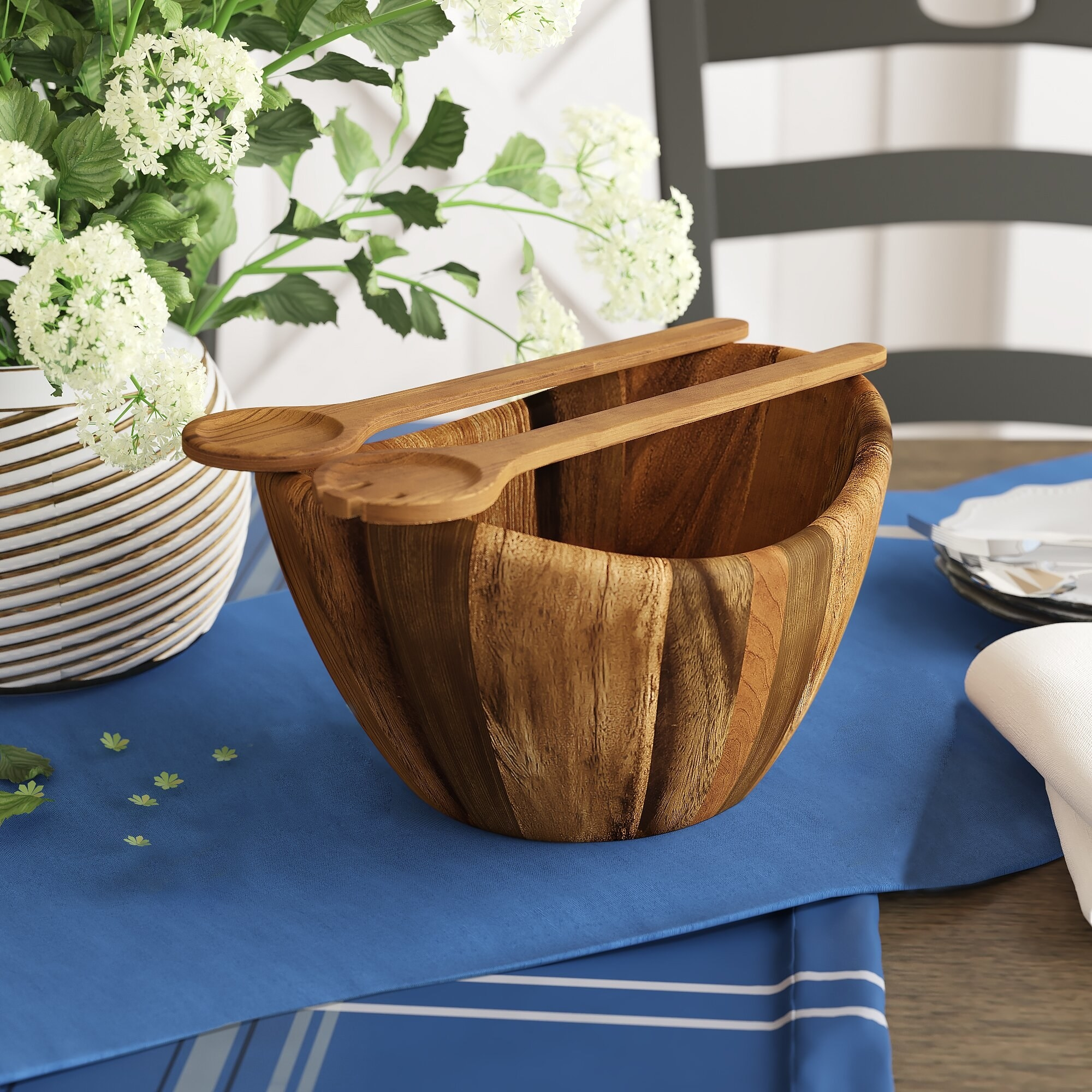 A wood grain finished salad bowl with matching spoon and fork serving utensils