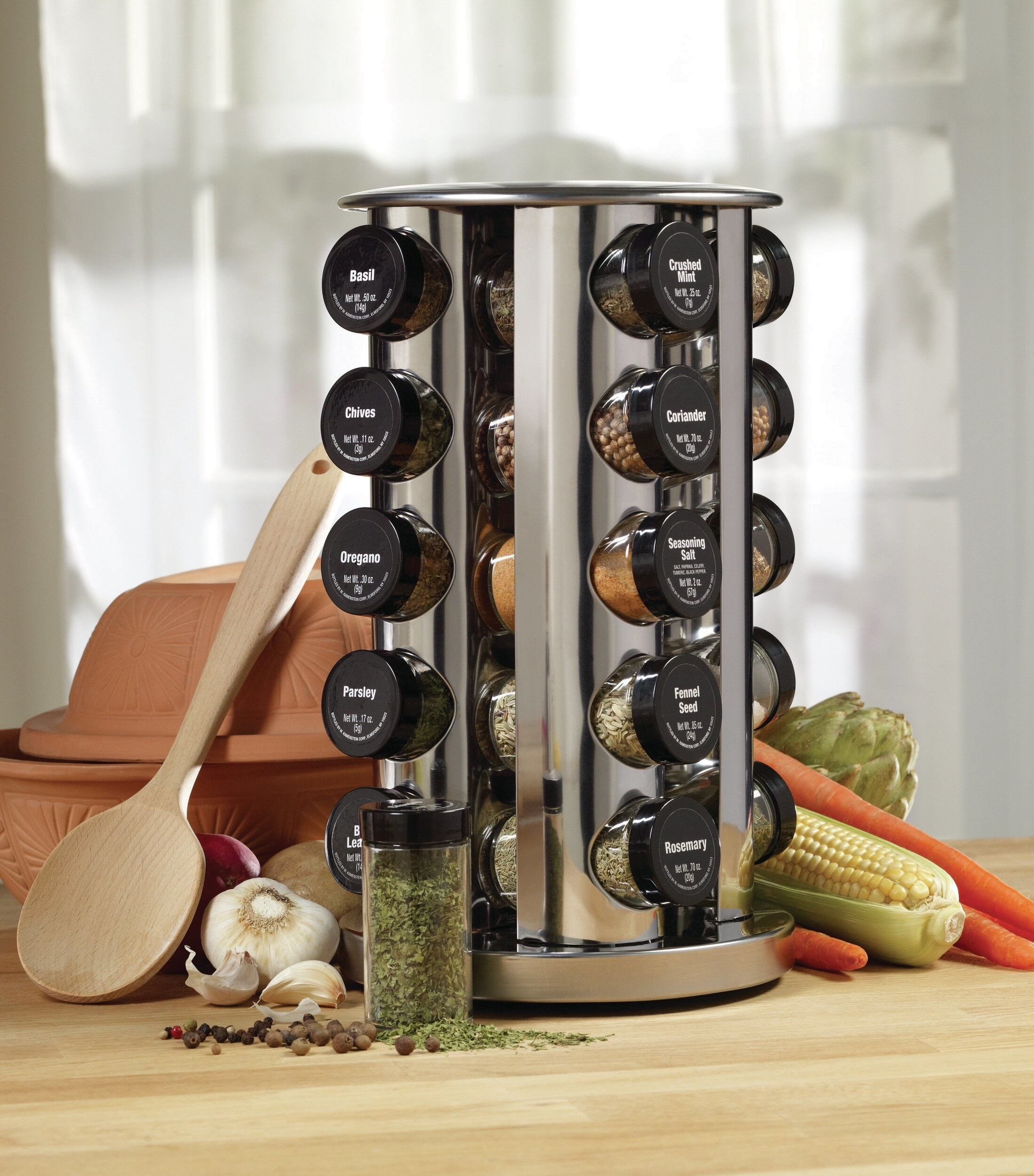 The metal revolving spice rack with clear jars with black labeled lids sitting five to a row