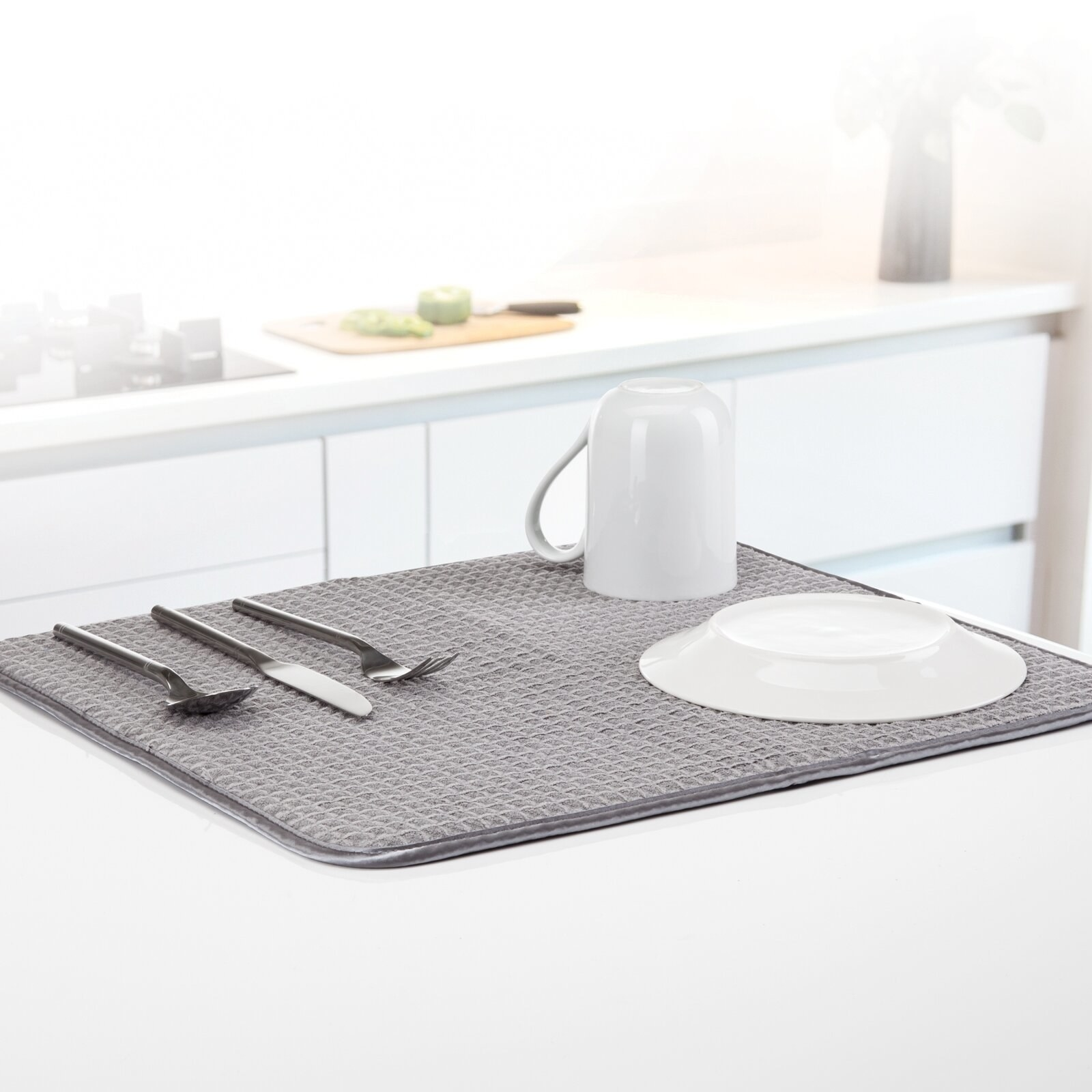 A gray drying mat with dishes laid on it