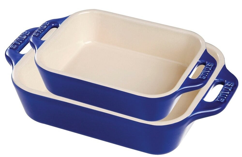 Two Staub baking dishes with blue exteriors, white interiors, and handles on the side