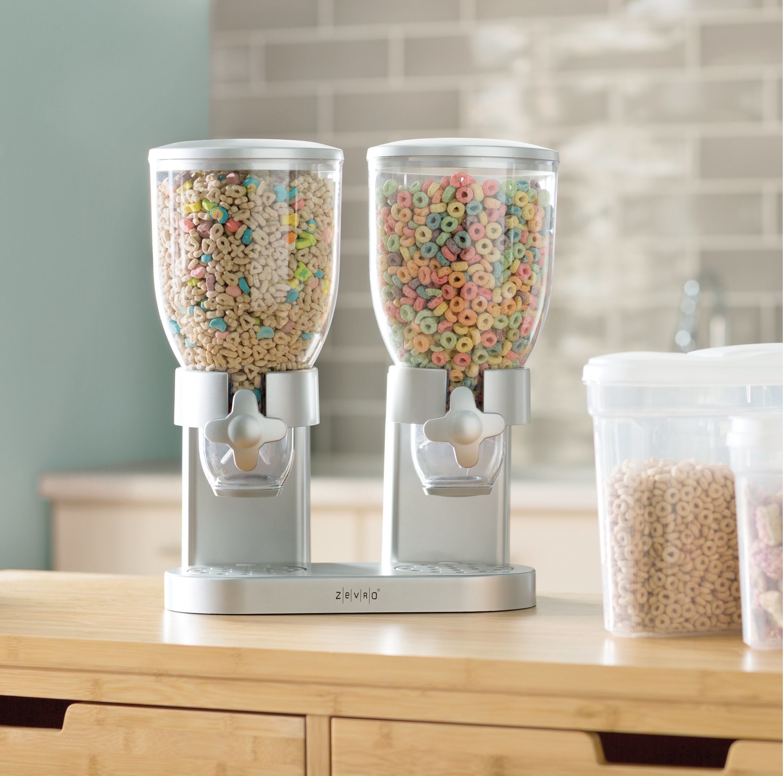Two silver cereal dispensers with clear storage vessels for the cereal and twist knobs to dispense it
